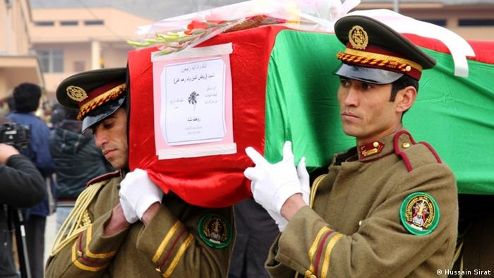 Soldier carry a coffin covered with an Afhgan flag Foto: Hussain Sirat/DW)