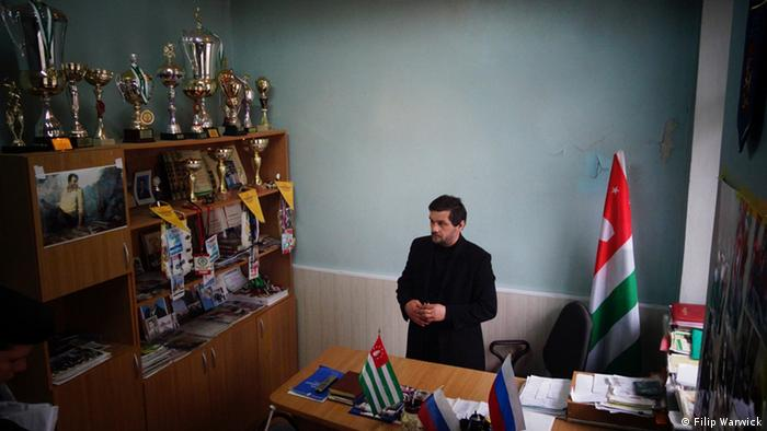 A picture of Djarnaz Beniya in his office with his medals. He is head of the Abkhaz wrestling committee.