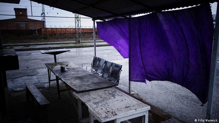 A picture of a deserted border crossing into Abkhazia from Russia with a purple curtain flapping in the breeze of a make shift structure.