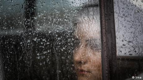 A woman looks out a window covered in rain drops