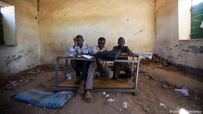 Three schoolboys sit at a desk in a damaged classroom in East Darfur, Sudan.