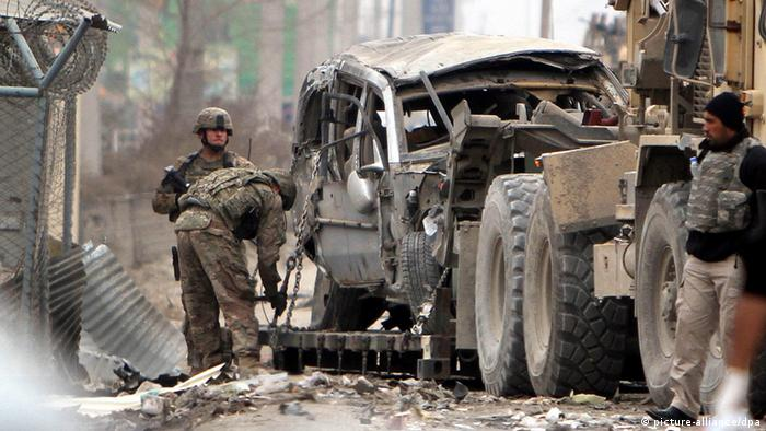 A car, destroyed by a suicide bomb attack, is towed in Kabul.