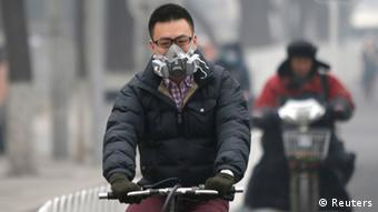 A man wearing a mask rides a bicycle in Beijing February 24, 2014.