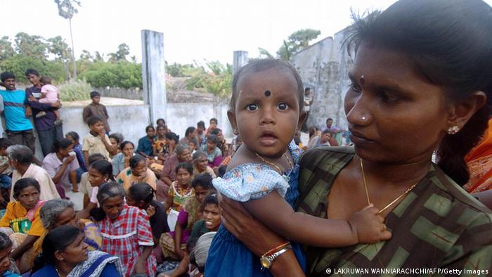 A Sri Lankan mother holds her child in a village Jaffna peninsula, 22 June 2006.