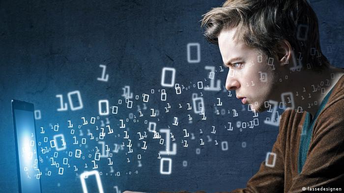 Symbolbild Hacker: Ein junger Mann starrt auf einen Monitor, aus dem die Zahlen 0 und 1 herausfliegen (Foto: Fotolia/lassedesignen)