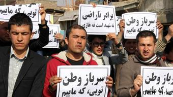Afghans men hold signs with Afghan writing on it (Foto: Hussain Sirat/DW)