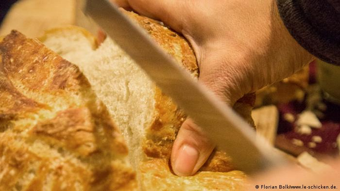 Close up of a hand cutting bread at a foodXchange Event Berlin Photo: Florian Bolk