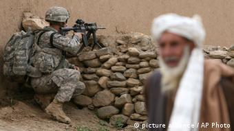 An Afghan man looks on as U.S. solider's of 3rd Brigade, 10th Mountain Division stands guard during a search operation in Nerkh district of Wardak province in west of Kabul, Afghanistan. A burst of strength by al-Qaida that is chipping away at the remains of Mideast stability now confronts President Barack Obama, testing his hands-off approach to conflicts in Iraq and Syria at the same time he pushes to keep thousands of U.S. forces in Afghanistan.