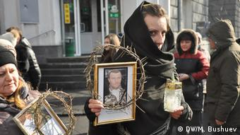 Women in black hold up portraits of relatives killed during the protests on the Maidan