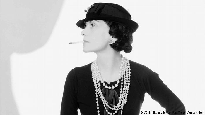 Coco Chanel wearing a hat and smoking a cigarette