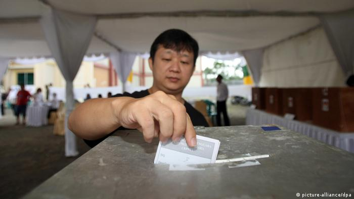 An Acehnese resident casts his vote into the ballot box in local elections in Aceh, Banda Aceh, Indonesia, 09 April 2012.
