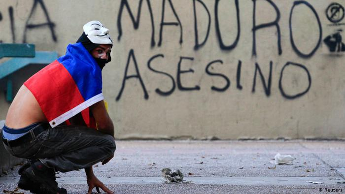 Venezuela protests 27.02.2014, crouching activist with flag and mask, Spanish graffiti that says Maduro assassin
