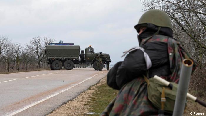 Ein bewaffneter Mann steht Wache am Zugang zum Belbek-Flughafen auf der Krim (Foto: Reuters)