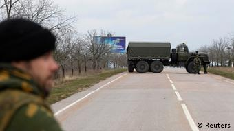 A road in Crimea is blocked by a truck and a soldier.
