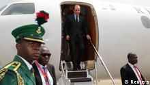 French President Francois Hollande (C) leaves his plane as he arrives at the Abuja airport February 27, 2014. Hollande attends the International conference on Peace and Security in Abuja, Nigeria's federal capital, as part of its Centenary celebrations. REUTERS/Philippe Wojazer (NIGERIA - Tags: POLITICS)