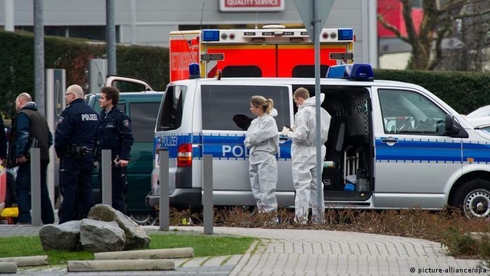 Полицейские в униформе и спецсотрудники в белых комбинезонах.