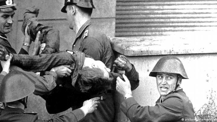 East German soldiers pick up Peter Fechter after he was shot while climbing over the Berlin Wall (picture-alliance/dpa)