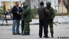 Armed men check journalists documents around the regional parliament building in the Crimean city of Simferopol March 1, 2014. U.S. President Barack Obama has warned Russia against any military intervention in Ukraine after the country's new leaders accused Moscow of deploying forces in the Crimea region. REUTERS/David Mdzinarishvili (UKRAINE - Tags: POLITICS MILITARY)