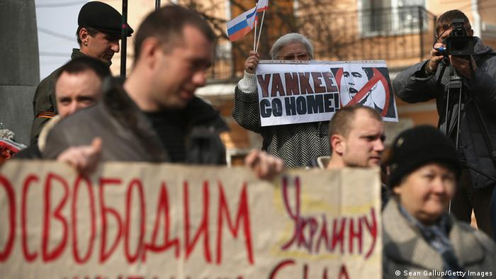 Pro-Russian sympathizers, including one man holding a sign that reads: We will free Ukraine from American occupation and an elderly woman holding another that reads: Yankee Go Home!, attend an anti-American rally hours (Photo by Sean Gallup/Getty Images)