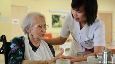 Uma cuidadora atende uma idosa