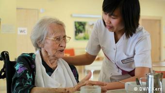 Вьетнамская сиделка помогает немецкой старушке
