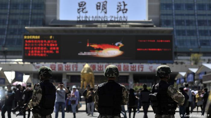 Armed policemen stand guard on the square outside the railway station in Kunming, China
