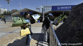 People arrive to lay wreaths outside the railway station in Kunming, southwest China's Yunnan province on March 2, 2014. Knife-wielding assailants left 29 people people dead and more than 130 wounded in an unprecedented attack at a Chinese train station, state media reported, blaming separatists from Xinjiang. CHINA OUT AFP PHOTO (Photo credit should read STR/AFP/Getty Images)