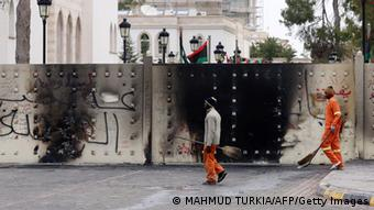 Two cleaners in orange overalls walk past the burned walls of the parliamentary compound in Tripoli