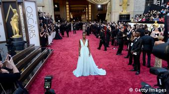 Lupita Nyong'o walking on the red carpet at the 2014 Oscars