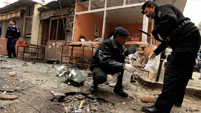 Policemen collect evidence from the site of a bomb attack at the district court in Islamabad March 3, 2014.