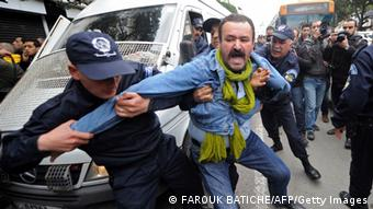 Police grab hold of a protester