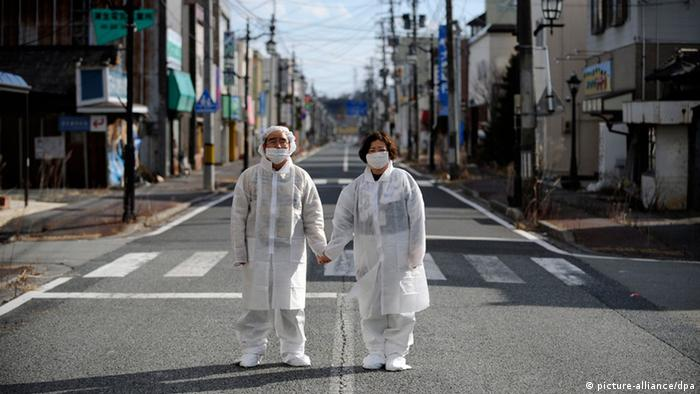 Wearing white protective masks and suits, Yuzo Mihara (L) and his wife Yuko pose for photographs on a deserted street in the town of Namie, Fukushima prefecture, Japan, 22 February 2013, in the Fukushima nuclear disaster exclusion zone.