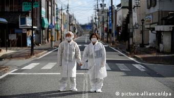 Two people in white protective suits stand in a deserted street (Foto: Franck Robichon/EPA)