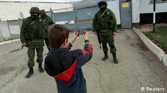 Ein Junge fotografiert die unbekannten Soldaten auf der Krim (Foto: Reuters)