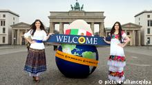 Die Models Johanna (l) und Klaudia posieren am 04.03.2014 vor dem Brandenburger Tor in Berlin in mexikanischen Kleidern mit einer aufblasbaren Weltkugel und einem übergroßen Sombrero. Die Aktion war Werbung für die bevorstehende Internationale Tourismusbörse (ITB), auf der Mexiko in diesem Jahr das offizielle Partnerland ist. Die diesjährige ITB findet von 05. bis 09.03. statt. Foto: Soeren Stache/dpa +++(c) dpa - Bildfunk+++