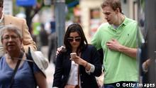 Symbolbild - Eine Frau schaut beim laufen auf ihr Handy
