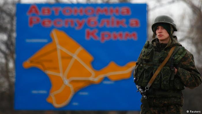 Украинский солдат на фоне плаката Автономная республика Крым