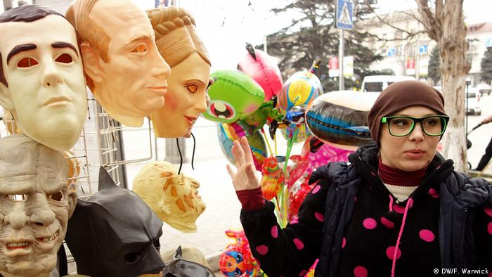 A picture of a rubber mask seller. The rubber masks are of politicians like Putin and Tymoshenko.