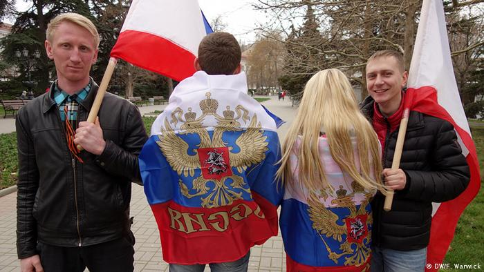 A group of friends with Russian and autonomous Crimean flags standing and posing for the camera.