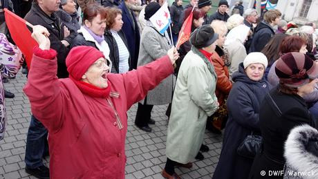 A picture of a pensioner in a crowd waving a Russian flag in a Pro Russian crowd.