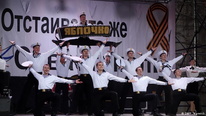 A picture of the Black Sea Fleet Ensemble during their Little Apple dance routine. They are dressed in naval routines.