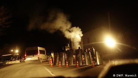 Road blocks on Crimean roads with car headlights and smoke at night.