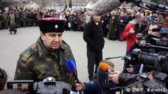 Surrounded by reporters, the Cuban Cossack's leader, Col. Sergei Savonin Yurievich explains why his forces are present.
