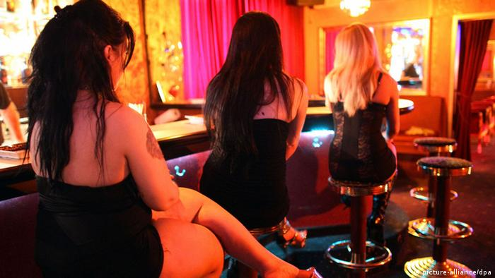 Three women sit on bar stools in a brothel in Germany