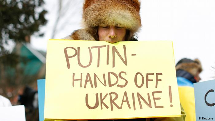 Protester with placard that reads: Putin, hands off Ukraine