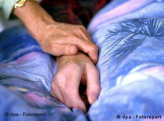 A woman holding the hand of a terminally ill patient at a hospice