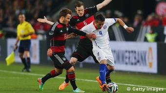 Mauricio Isla of Chile is challenged by Marcell Jansen and Mario Goetze (R-L) of Germany during the interntional friendly match between Germany and Chile at Mercedes-Benz Arena on March 5, 2014 in Stuttgart, Germany. (Photo by Alex Grimm/Bongarts/Getty Images)