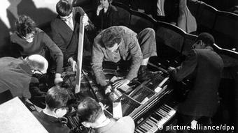 Black and white photo of a group of people around a piano. With hammers and other devices to create noise, Ben Patterson was one of the participating artists the 1962 'International Fluxus Festival of the Newest Music' in Weisbaden Photo: picture-alliance/dpa