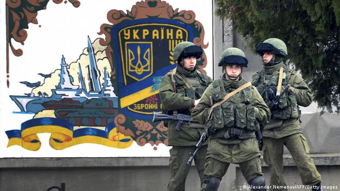 Three armed soldiers in green uniforms with helmets outside a Ukrainian navy base (Photo: ALEXANDER NEMENOV / AFP / Getty Images)