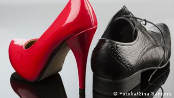 A red high heel with a black men's shoe